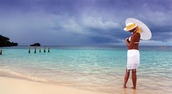 girl with an umbrella on a beach on a cloudy day