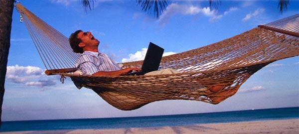 man-laughing-hammock-sea-laptop.jpg