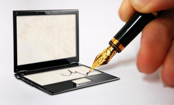pen writing on a laptop