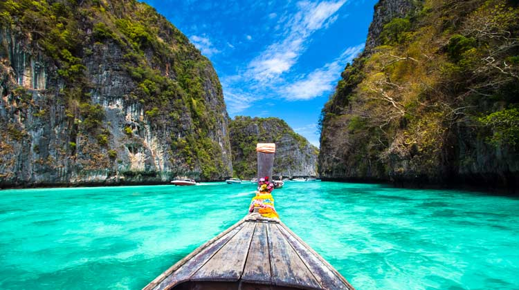 boat in between two islands in beautiful tropical sea in thailand