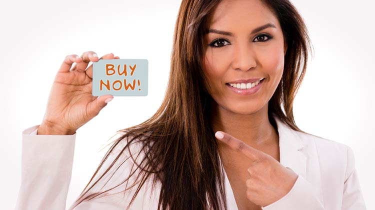 saleswoman holding up a card with buy now written on it