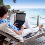 guy with laptop on a deck near the sea