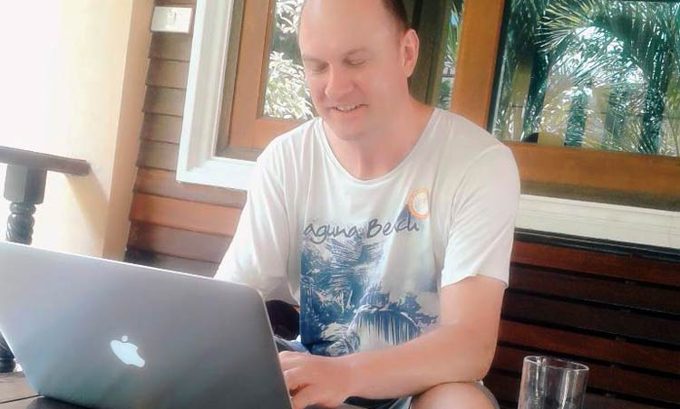 rob cubbon working on a laptop on balcony